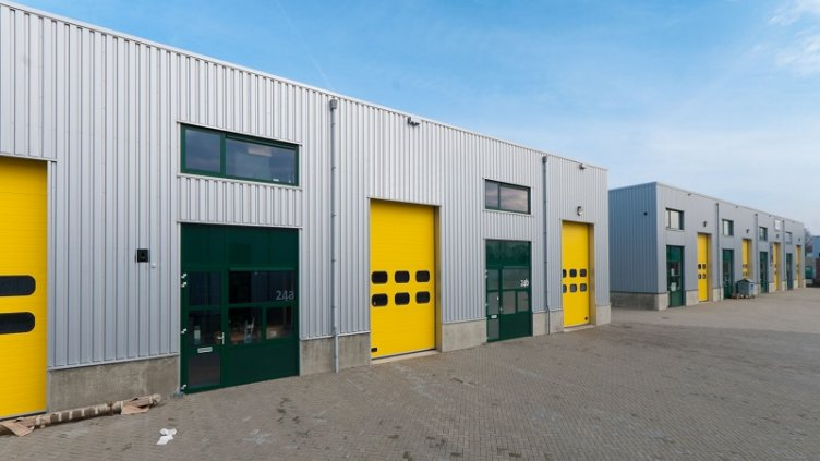 8903896 - industrial warehouse with green and yellow roller doors