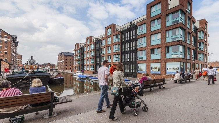 Gloucester, England, UK: 17 April 2011 - An apartment building at the refurbished Gloucester Docks. People are strolling around.