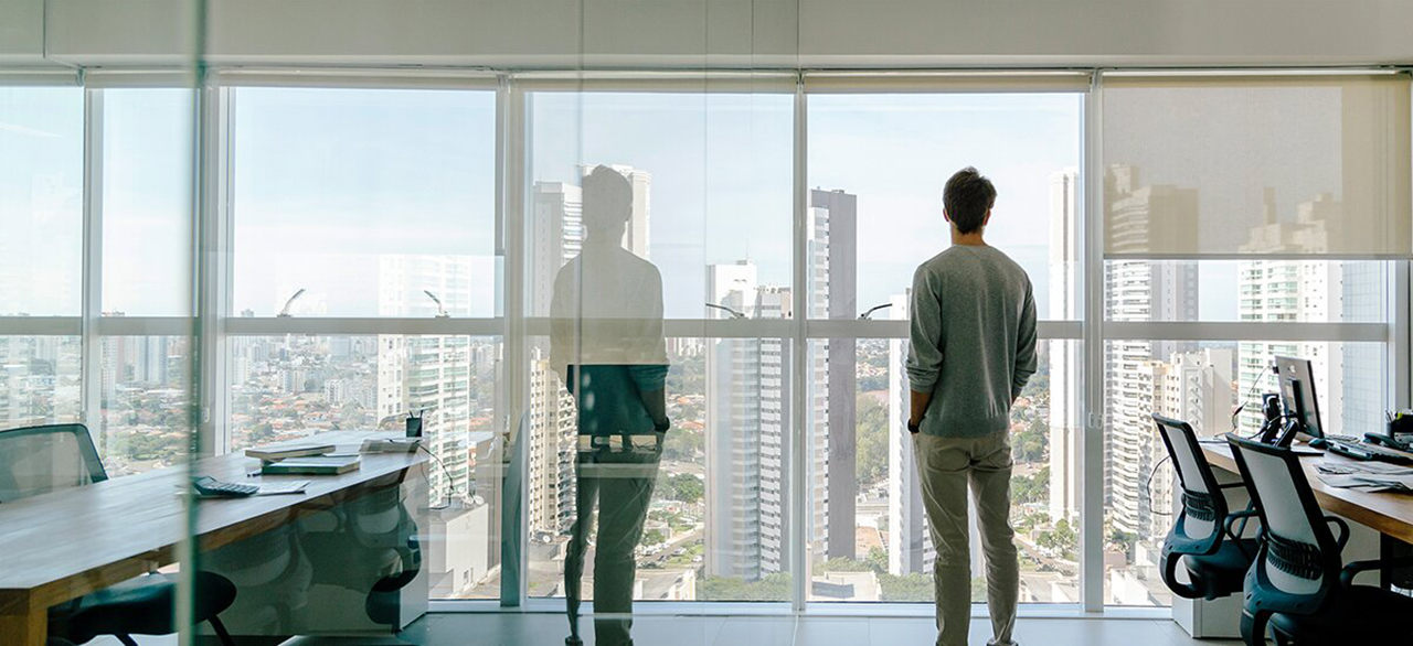 young man looks out of office window over city