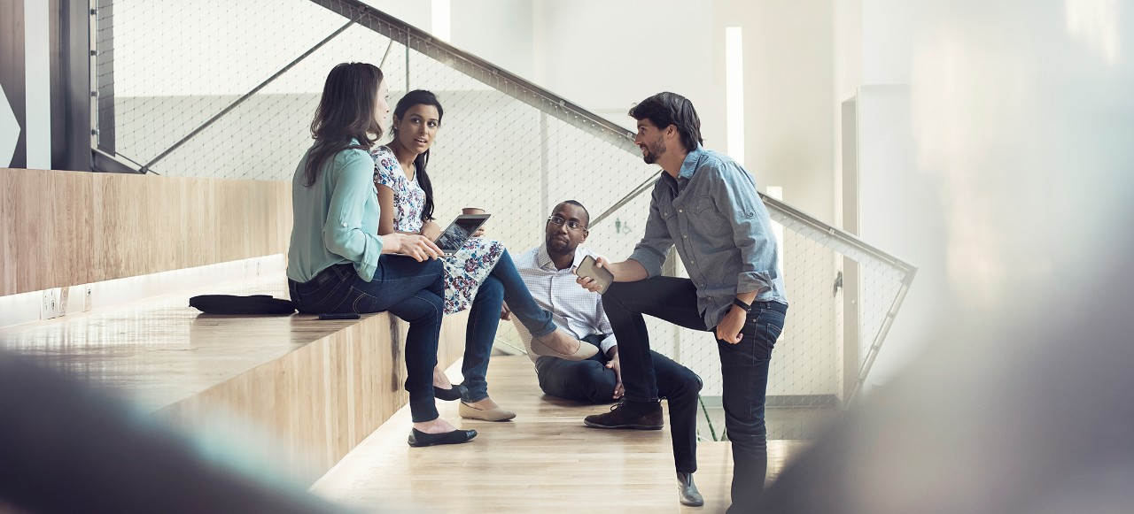 Young business people discussing, sitting on stairs